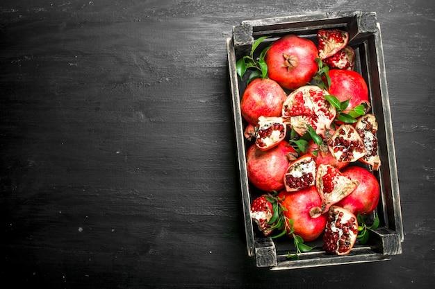 Świeże granaty w pudełku na czarnej tablicy