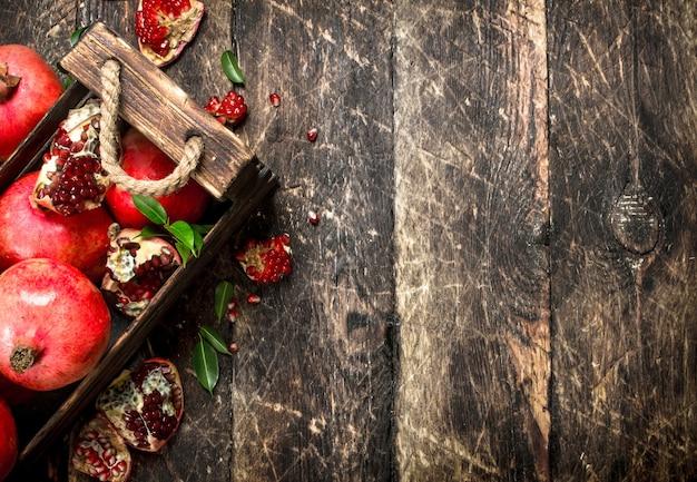 Świeże granaty w starym pudełku. na drewnianym stole.