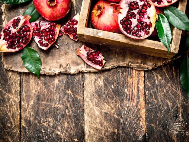 Świeże granaty w starym pudełku na podłoże drewniane