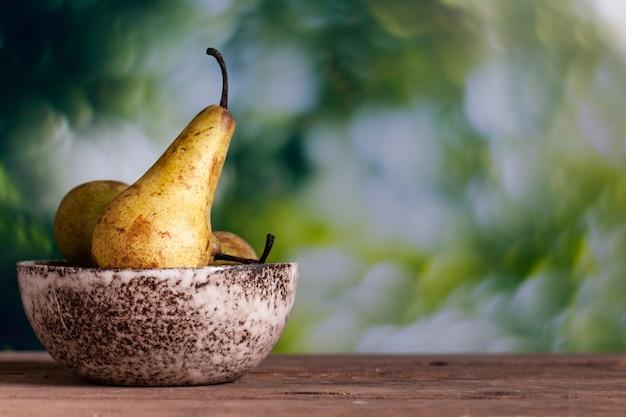 Świeże gruszki w ceramicznej misce na drewnianym stole