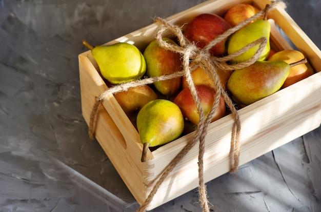 Świeże gruszki w drewnianym pudełku w słonecznej szarości