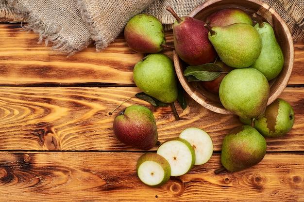Świeże gruszki w drewnianym talerzu i plastry gruszki na rustykalnym stole.