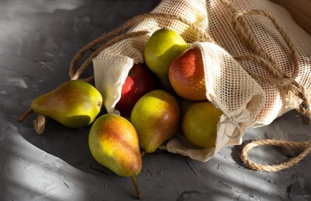 Świeże gruszki w siateczkowej torbie na zakupy na szarym słonecznym tle