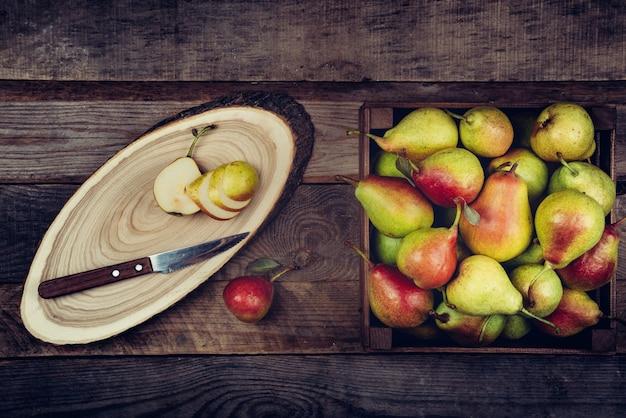 Świeże gruszki z liśćmi w drewnianym pudełku na drewnianym.