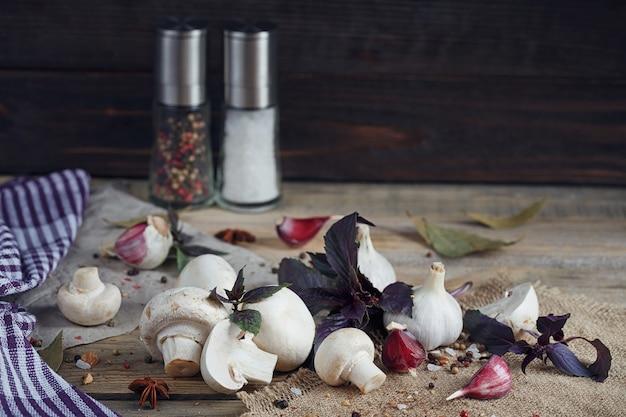 Świeże grzyby i czosnek na rustykalnym drewnie
