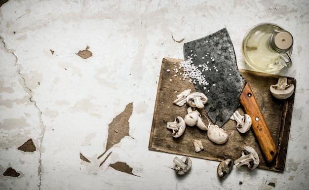 Świeże grzyby siekane siekierką na desce z przyprawami i oliwą na rustykalnym tle.
