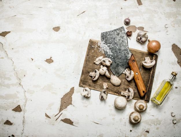 Świeże grzyby siekane siekierką na desce z przyprawami i oliwą