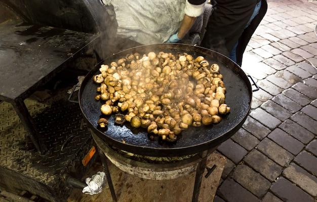 Świeże grzyby smażone na dużej metalowej patelni na zewnątrz