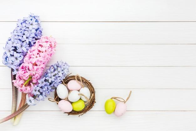 Świeże hiacynty i ozdobne pisanki w małym gnieździe na białym stole. widok z góry, miejsce na kopię