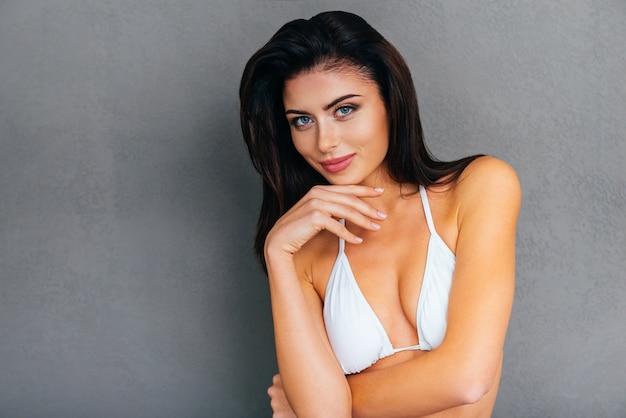 Świeże i piękne. atrakcyjna młoda uśmiechnięta kobieta w białym bikini trzymająca rękę na brodzie i patrząca w kamerę, stojąc na szarym tle