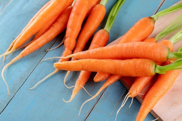 Świeże i słodkie marchewki na niebieskim drewnianym stole