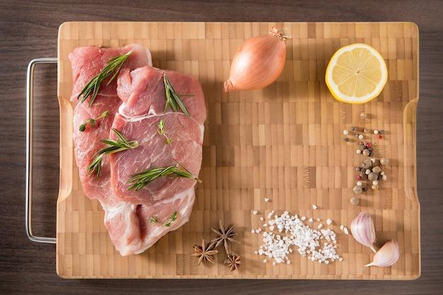 Świeże i surowe mięso cielęce steki z przyprawami w rzędzie gotowe do przyrządzenia