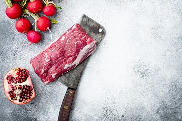 Świeże i surowe mięso wołowe. cały kawałek polędwicy ze stekami i przyprawami gotowy do gotowania, na starym nożu rzeźniczym, na szarym tle kamienia, widok z góry na płasko, z kopią miejsca na tekst