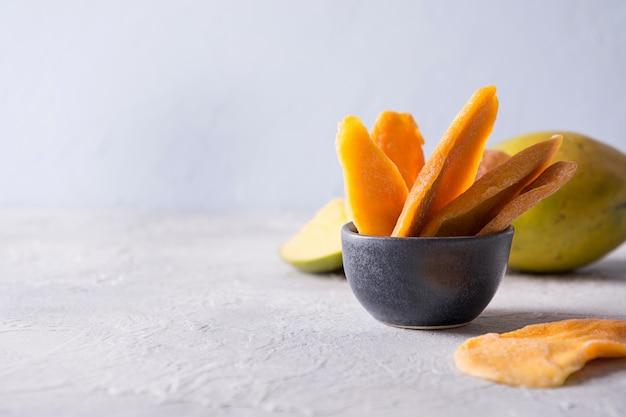 Świeże i suszone chipsy z mango na świetle. ścieśniać.