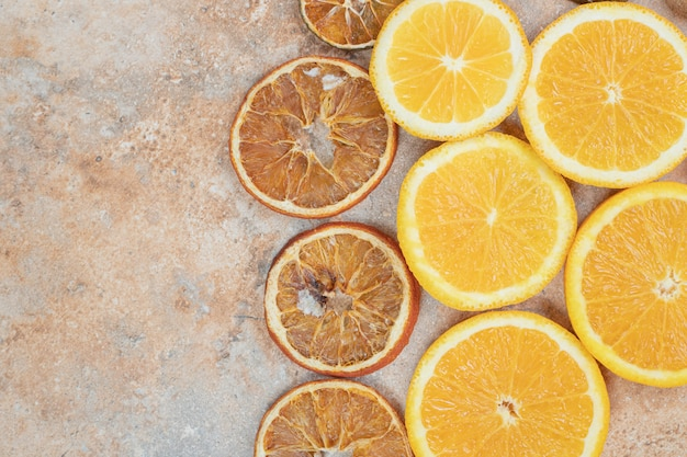 Świeże i suszone plastry pomarańczy na tle marmuru.