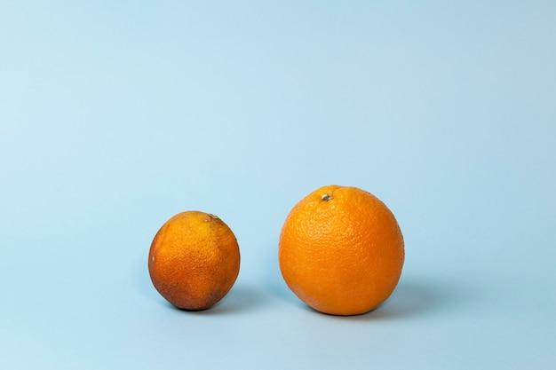 Świeże i zepsute pomarańcze na jasnoniebieskim tle