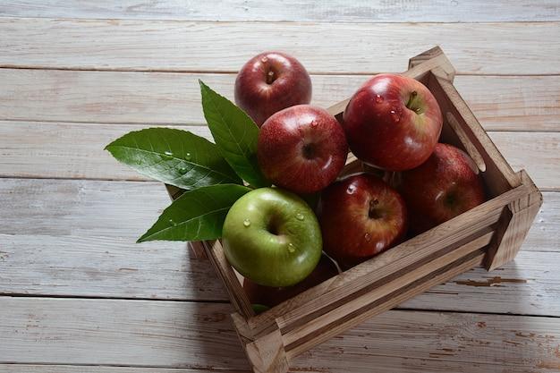 Świeże jabłka czerwone i zielone w drewnianym pudełku w stylu rustykalnym. zdrowe jedzenie