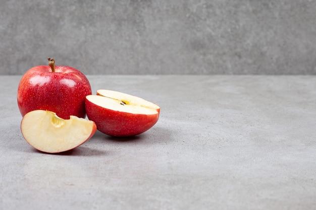Świeże jabłka ekologiczne. całe lub pokrojone czerwone jabłka na szarym stole.