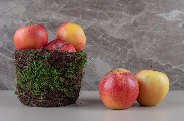 Świeże jabłka w misce na marmurze i obok niej