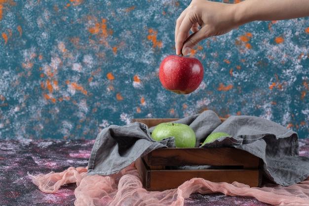 Świeże jabłka w rustykalnym drewnianym pojemniku.