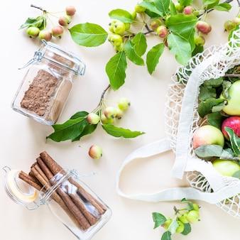 Świeże jabłka w siatkowej torbie na zakupy z gałęzi jabłek i cynamonu