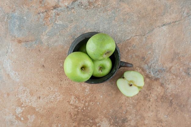 Świeże jabłka ze starożytnym kubkiem na marmurze