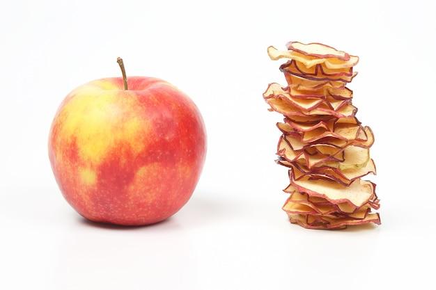 Świeże jabłko i stos suszonych plasterków jabłka na białej przestrzeni