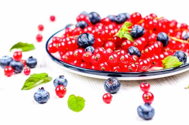 Świeże jagody i czerwone porzeczki z liśćmi mięty w drewnianej misce na płótnie
