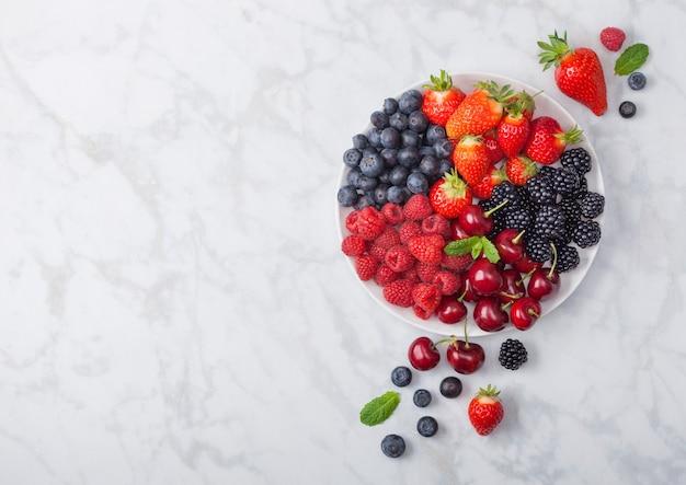 Świeże jagody organiczne letnie wymieszać w białej płytce na marmurowym tle. maliny, truskawki, jagody, jeżyny i wiśnie. widok z góry