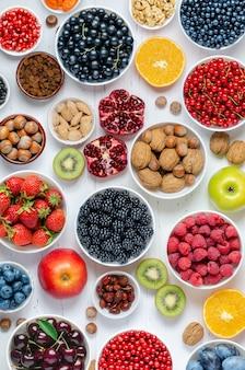 Świeże jagody owoce orzechy na białym drewnianym tle koncepcja zdrowego odżywiania zawiera v