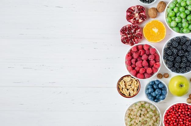 Świeże jagody, owoce, orzechy na białym tle drewnianych. pojęcie zdrowego odżywiania. żywność zawiera witaminy i pierwiastki śladowe. skopiuj miejsce.