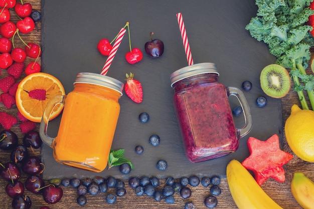 Świeże jagody smoothy i pomarańczowy zdrowy napój w szklanych słoikach ze składnikami