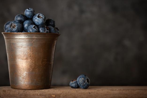 Świeże jagody w filiżance vintage na tle rustykalnym.