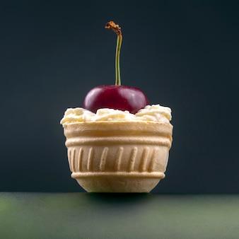 Świeże jagody wiśni w śmietanie mlecznej leżą w koszyku waflowym. zdrowa żywność na śniadanie. owoce roślinności. deser owocowy