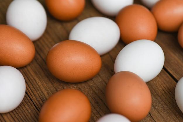 Świeże jaja kurze i jaja kacze na drewnianym tle, białe i brązowe jajka z farmy
