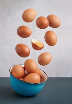 Świeże jaja latające nad niebieską miską, odizolowane