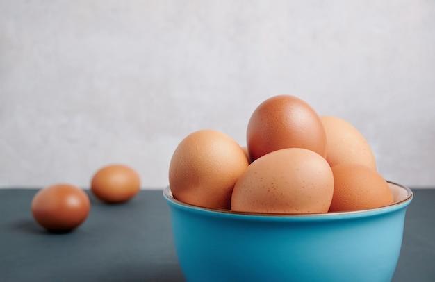 Świeże jaja w niebieskiej misce z miejsca na kopię