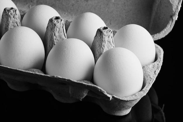 Świeże jajka w otwartym polu na czarnym tle