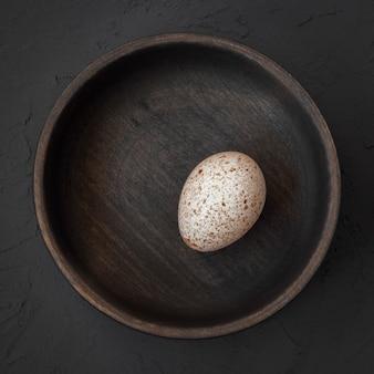 Świeże jajko z indyka leży w drewnianej misce