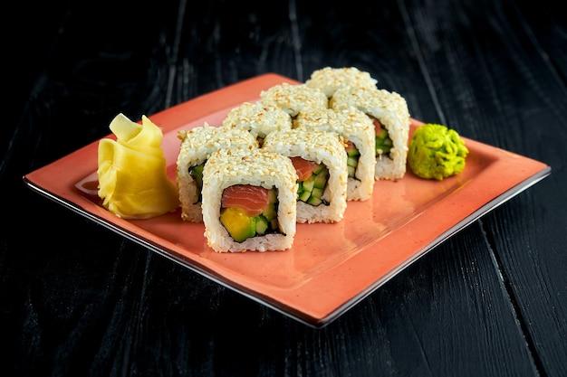 Świeże, japońskie roladki sushi z awokado, ogórkiem i łososiem podane na talerzu z wasabi i imbirem na ciemnym tle.