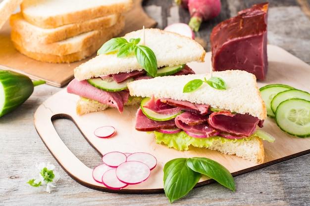 Świeże kanapki z białego chleba z pastrami, ogórkiem, rzodkiewką i bazylią na desce do krojenia. amerykańska przekąska. styl rustykalny