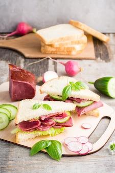 Świeże kanapki z pastrami i warzywami na desce do krojenia. amerykańska przekąska. styl rustykalny.