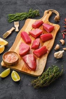 Świeże kawałki fileta z tuńczyka z przyprawami i ziołami na drewnianej desce do krojenia
