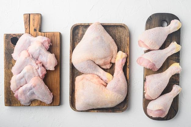 Świeże kawałki mięsa drobiowego zestaw mięsa drobiowego gospodarstwa, na drewnianej desce do krojenia, na białym stole, widok z góry płasko leżał