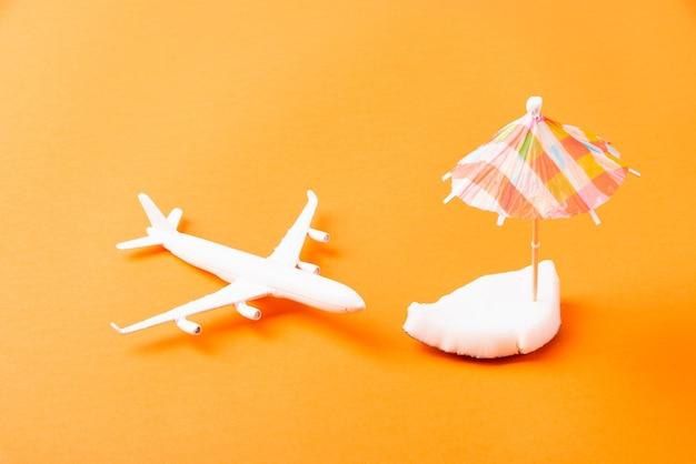 Świeże kawałki orzecha kokosowego, samolot, model samolotu i parasol słoneczny