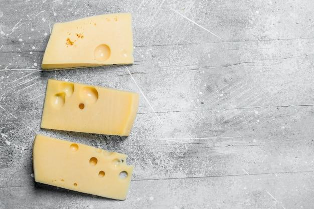 Świeże kawałki sera. na rustykalnym tle.