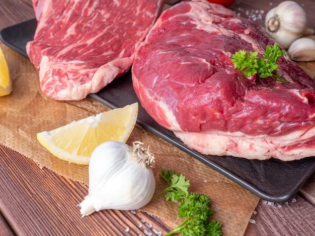 Świeże kawałki surowego marmurowego mięsa na drewnianym tle. widok z boku. warzywa i przyprawy dookoła