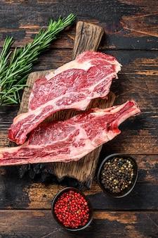 Świeże kawałki surowego mięsa wołowego na pokładzie rozbioru. ciemne tło drewniane. widok z góry.