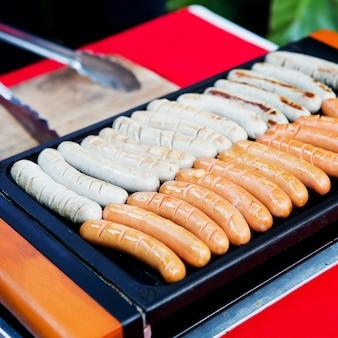 Świeże kiełbasy i hot dogi z grilla na zewnątrz na grilla gazowego.