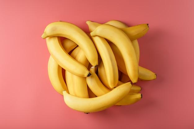 Świeże kiść żółtych bananów na białym tle na różowym tle. minimalistyczna koncepcja. wolna przestrzeń